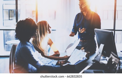 Young team of coworkers making great meeting discussion in modern coworking office.Hispanic businessman talking with two business womans.Teamwork concept.Horizontal,blurred background,flares effect