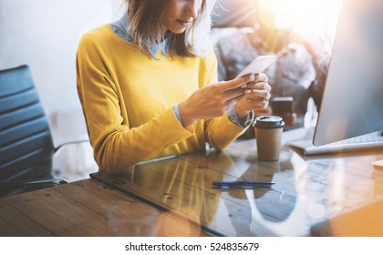 Young team of coworkers using together mobile devices in modern coworking space. Beautiful girl sending message with smartphone.Horizontal. Blurred background,flares effect