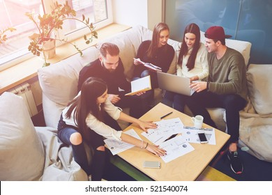 Young team of freelancers searching information making business tasks consulting with expert. Students preparing presentation using technology modern laptop wireless internet connection in coworking