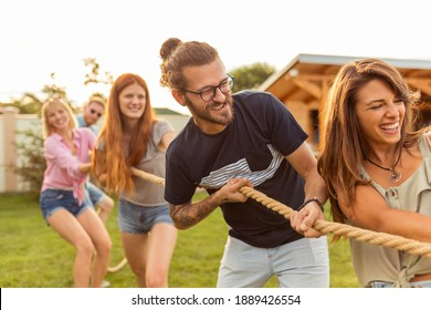 Young team having fun competing in tug of war game while on team building trip; group of friends having fun while participating in rope pulling competition