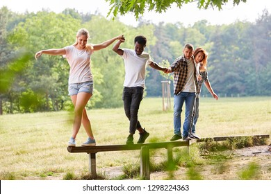 Young team helps balance on a beam at teambuilding event