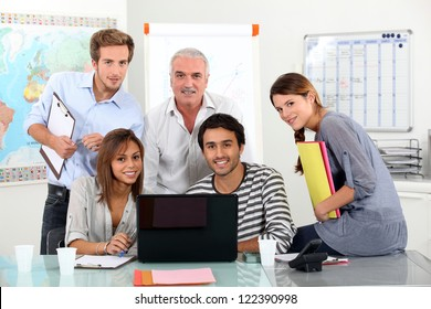 Young team of people sitting around a laptop with an older guy
