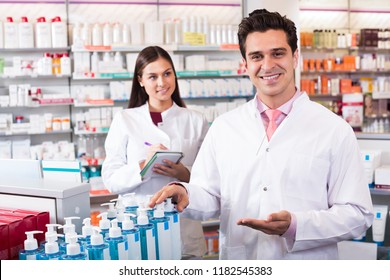 Young team of a pharmaceutist and technician working in the chemist shop