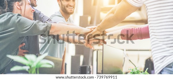 Young team putting hands up for new startup in creative office - Cheerful people giving strength motivation - Soft focus on woman with red pullover hand - Co-working and teamwork concept