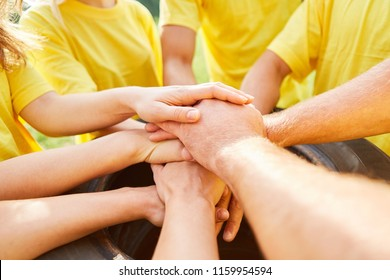 Young team stacks hands on each other for teambuilding and team development