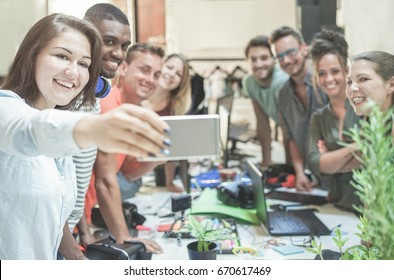 Young teamwork taking selfie in creative office - Blog co-workers having fun with rends technologies - Team,unity,loyalty,youth,trends and friendship concept - Focus on woman face with mobile phone