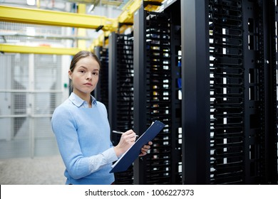 Young technical staff of mining farm with clipboard and pen making working notes in data storage room