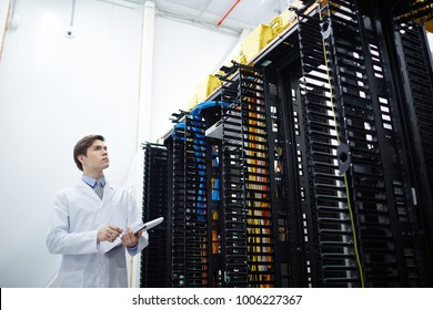 Young technical worker of data center making revision of hardware in storage room