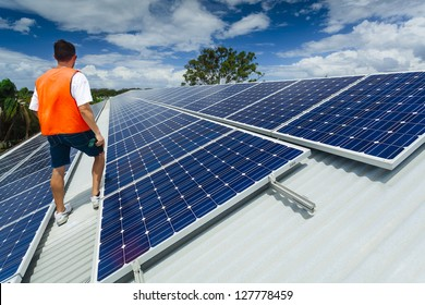 Young technician inspecting solar panels on factory roof