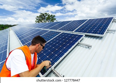Young technician installing solar panels on factory roof