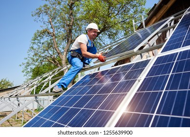 Young technician in protective helmet on tall metal platform installing heavy solar photo voltaic panel on green tree background. Stand-alone solar panel system installation, dangerous job concept.