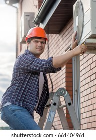 Young technician repairing outside air conditioning unit