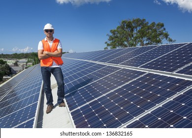 Young technician standing with solar panels on factory roof