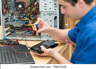 a young technician working on broken computer in his office