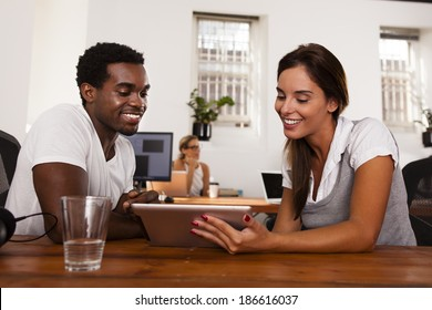 Young technology entrepreneurs discussing a tablet computer in a startup office