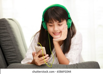 Young teen Asian girl listening to music with headphone and smarthphone at home with happiness manner, concept for modern life of  teenager free time at home