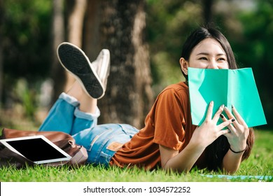 A young or teen asian girl student in university smiling and reading the book and look at the tablet or labtop computer in summer holiday.