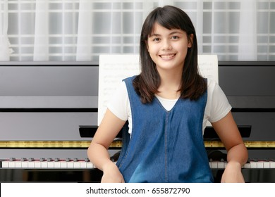 Young teen beautiful black hair Asian girl sitting at piano with eyes contact to camera
