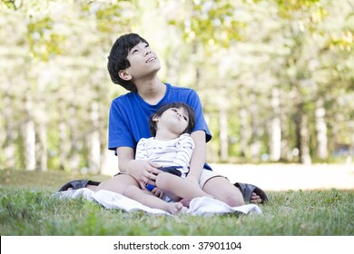 Young teen boy caring for disabled brother, looking up into sky