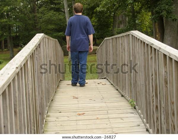 young teen boy crossing a wooden bridge