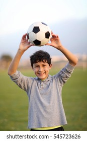 Young teen boy with football in the playing field during the golden hour - shallow depth of field