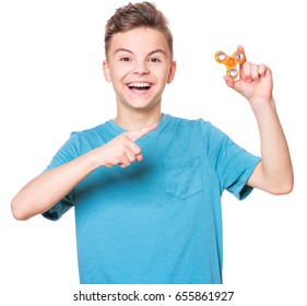 Young teen boy holding popular fidget spinner toy - close up portrait. Happy smiling child playing with Spinner, isolated on white background.