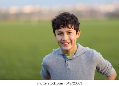 Young teen boy in the playing field during the golden hour - shallow depth of field - copy space left