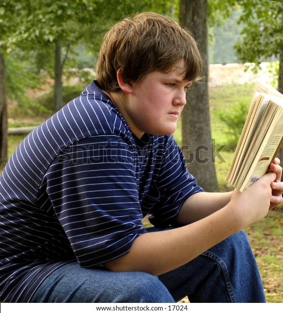 Young teen boy reading a book in an outdoor setting