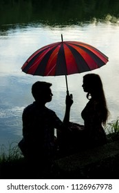 Young teen couple with umbrella, silhouette