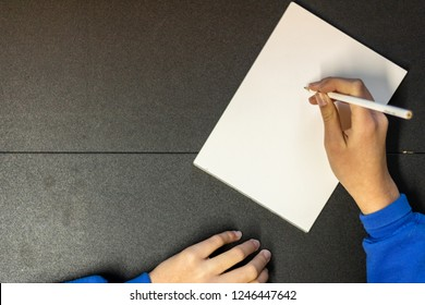 Young teen drawing on a notebook. With copy space on the left side for text and images.