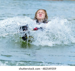 Young teen girl being pulled out of the water to start skiing. Her faces shows her determination.