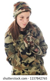 A young teen girl in camouflage happily contemplating the shoot as she stands with her fingers locked in a gun position.  Isolated on white.