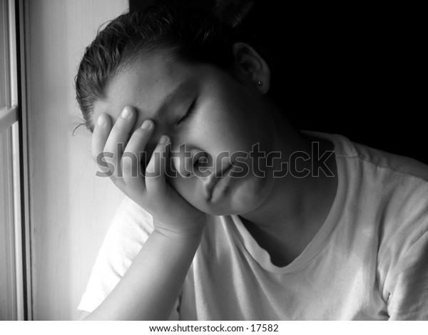 young teen girl with head in her hands in black and white