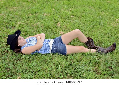 Young teen girl lying in the grass with western style clothing.