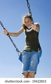 A young teen girl on a playground swing in front of a blue sky