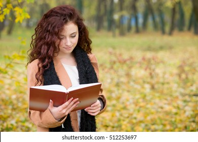 young teen girl reading a book in a park in autumn