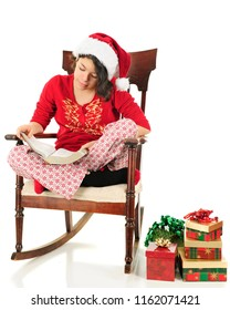 A young teen girl reading the Christmas story in her Bible as she sits in a vintage rocker with gifts by her side.  She's wearing a Santa hat and her pajamas.  On a white background.