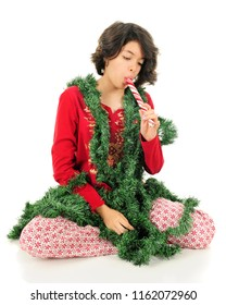 A young teen girl sucking on a large peppermint log while sitting in her pajamas and draped in Christmas garland.  On a white background.
