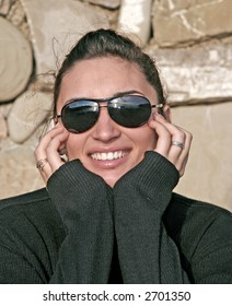 young teen girl with sun glasses smiling with the hands at face