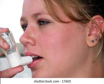 young teen girl using an asthma inhaler