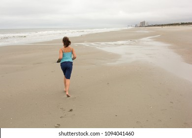Young teen girl walks on a cloudy beach in Myrtle Beach SC making the best of a rainy day on vacation