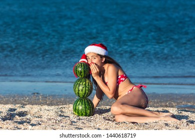young teen girl whispering something to snowman from watermelons. summer christmas on beach