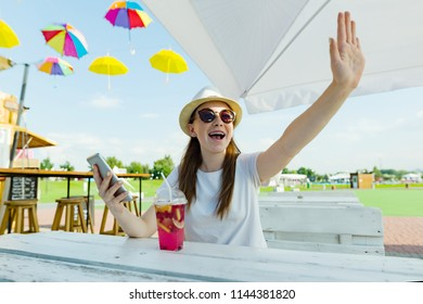 Young teen girls with mobile phones. Sit in a street cafe, sunny summer day in recreation and entertainment area, girl waving her hand greets