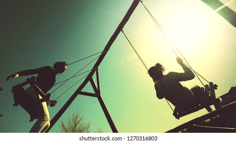 Young teen girls sitting on a swing at sunset