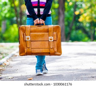 Young teen girt with suitcase in a park in sunny day