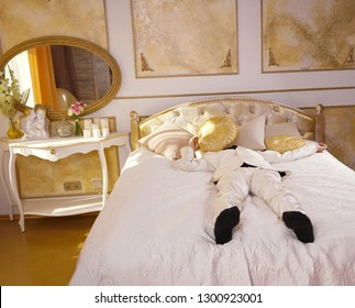 young teen guy wearing white business suit and lying on the bed in his Golden room, stretching and yawning
