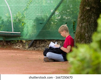Young teen kid sits on ground under a tree, and reads from folded papers.