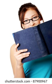 Young teen student in glasses holding open book over white background.