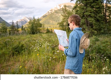 Young Teen Traveler wearing hat, look at map relaxing outdoor with rocky mountains on background. Summer vacation, active healthy lifestyle and hiking concept. Family weekend camping. Boy's tourism.
