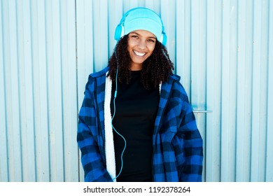 Young teen woman listening to music against a blue wall